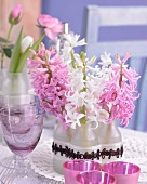 Pink and white hyacinths in small glass bottles
