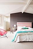 Schlafzimmer mit Doppelbett & gemustertem Kopfteil vor Trennwand aus Holz