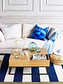 Sitting area in living room with white sofa, blue and white striped carpet and coffee table with maritime decoration