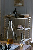 Collection of stone ornaments and books on delicate shelves; bottle and liqueur glass in foreground