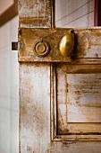 Small, oval brass doorknob on old, shabby-chic interior door