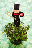 Iron cross oxalis in plant pot with chimney sweep figure (both bring good luck)