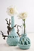 Two vases with crocheted covers holding one white carnation each