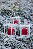 Drei weiße Metallwindlichter mit roten Kerzen