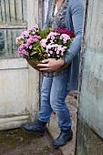 Frau trägt ein Blumenarrangement mit Chrysanthemen