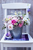 Bouquet of roses with pink yarrow and chamomile in zinc bucket