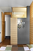 Modern bedroom with partial wood cladding and illuminated bathroom block - devotional objects hanging on grey-painted wall