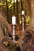 Candles with wreaths of berries in autumnal woodland