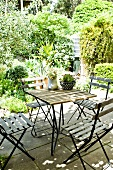Wood and metal terrace table and folding chairs in front of Mediterranean garden
