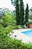 Stühle am Pool in mediterranem Garten