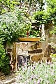 Birdbath on rough stone block in Mediterranean garden