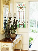 Table lamp made from antique sculptures on a console table in front of an entry door with colorful leaded glass panel