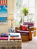 Coffee table with books and antique wicker chair upholstered in colorful fabric in a conservatory