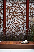 Afternoon tea in courtyard garden - purist wooden bench in front of artistic screen