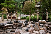 Japanese rock garden with fences made of bamboo and twine and stone lamp in background