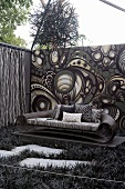 Expansive wicker sofa against back wall with psychedelic black and white pattern below suspended artwork made from twigs