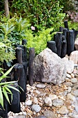Decorative path border of black, carbonised wooden posts and boulders in garden