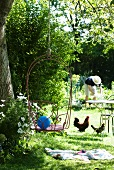 Gartenidylle - Drahtstuhl an einem Seil im Baum hängend, Hühner unter Bistrotisch und arbeitende Person im Hintergrund
