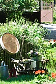Gardening utensils and planters in wooden handcart next to garden fence