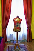 Vintage tailor's dummy in front of window with gathered red curtains and translucent drape