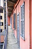 Balcony of old apartment house with pink facade and grey-blue shutters