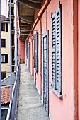 Laubengang an altem Wohnhaus mit rosa Anstrich und grau-blauen Fensterläden
