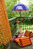 Exotic seating area on balcony with blue parasol with beaded fringe and wedge cushions on colourful blanket