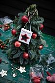 Christbaum mit roten Äpfeln und Schild Merry Christmas