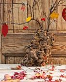 Herbstdeko mit Baumrinde, Zweigen, Blättern und Hagebutten