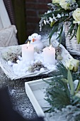 Winter arrangement with candles, snowman figurine and flowers