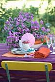 Vorbereitungsstadium eines sommerlich gedeckten Gartentisches mit Bougainvillea auf violettem Tischtuch und Stuhllehne in der Komplementärfarbe Gelb