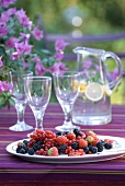 Mixed summer berries on striped purple tablecloth in front of water jug and glasses with bougainvillea flowers in hazy background