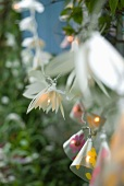 Lighted string of fairy lights with shades shaped like various flowers as decoration for garden party