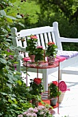 Romantic, country-house-style seating area on terrace decorated in shades of pink combined with white bench and potted plants on red side table