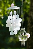 Wind chime made from Capiz shells and glass bead pendant lantern in garden
