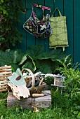 Korb mit Gartenutensilien auf einem Holzblock im Garten