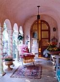Rosa getönter Kalkstein-Arkadengang mit exotisch angehauchter Terrassendeko vor großer Rundbogen-Flügeltür