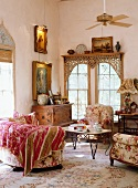 Romantic, antique sitting area with floral upholstered furniture and vintage chest of drawers in front of a lattice window with an oriental touch