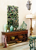A collection of assorted vases and plates on an antique sideboard with a fringe border under an abstract stained glass panel