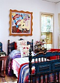 Antique, blue country bed with colorful bed linen under a modern, Pop Art painting