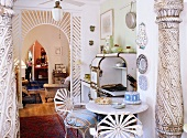 Decorated columns and a semi-transparent arched hallway separating the kitchen with a vintage wood stove and eye catching iron chairs in the living area
