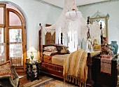 Style mix - antique canopy bed with transparent curtain in a bedroom with oriental influences
