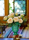 Bouquet of roses in a turquoise terra cotta vase on a striped table runner