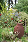 Clay amphora in front of flower bed with a riot of growth and trees in the background