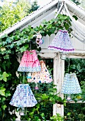 Hand-crafted lampshades covering tealight holders in garden
