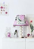 Alter Lampenschirm in neuem Design - mit Zeitungspapier und Papierblumen beklebt, am Rand mit Bändern verziert