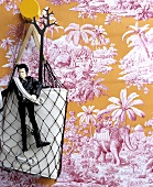 Bag in net and cult action figure against Toile de Jouy wallpaper