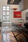 Designerstil und Bauhaus in offener Küche mit traditionellem Flair - Schwarzer Küchenblock auf Terrazzoboden mit Ornamentmuster vor Esstisch im Bauhausstil