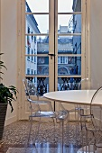 Ghost chairs at round Bauhaus dining table in front of balcony door with view of neighbouring building