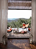 Candle lanterns flanking terrace doors; panoramic view from terrace with inviting butterfly chairs and drinks on tray table